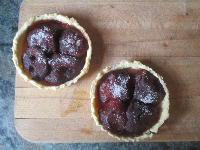 two cooked apple tarts on cutting board