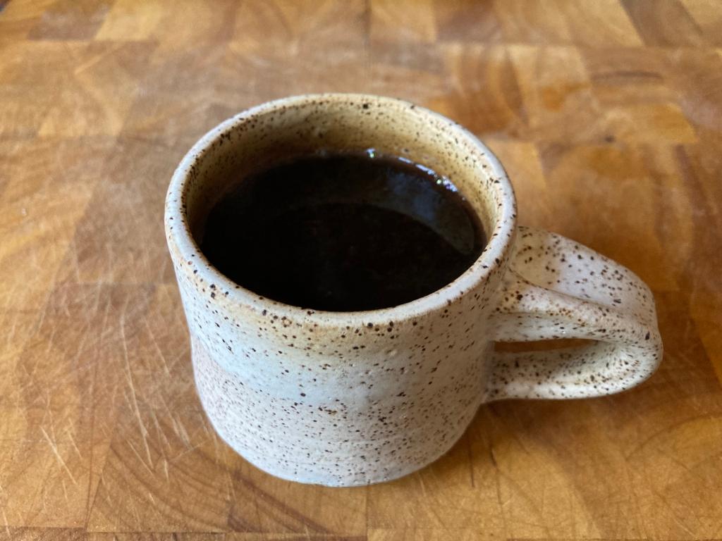 brewed coffee in white mug on cutting board